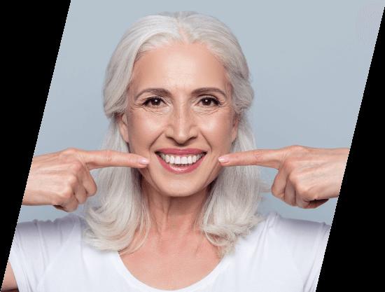 senior woman pointing to her white smile