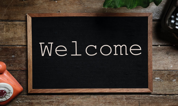 "A black letter board with the word ""Welcome"" on a wooden table next to an old-fashioned phone and leaf"
