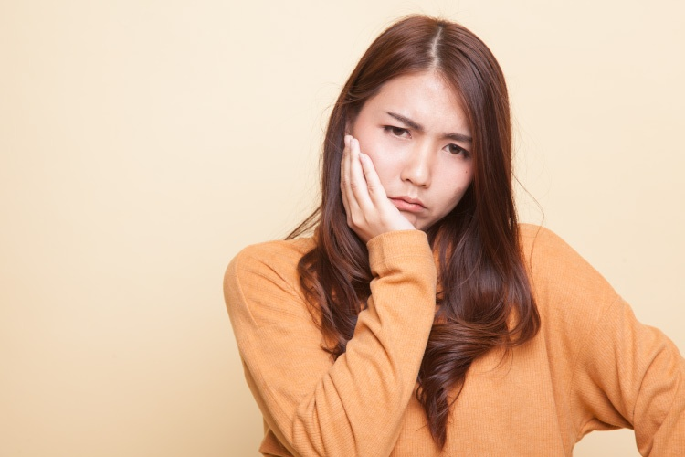 Brunette young woman wearing a gold shirt cringes and touches her cheek due to a toothache emergency