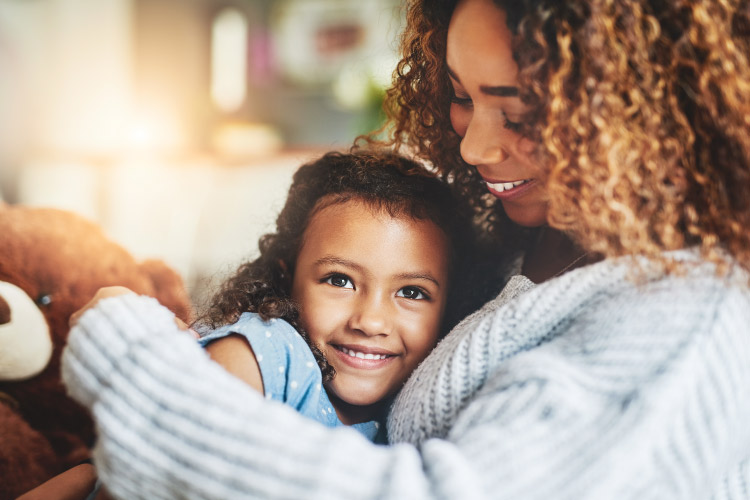 Curly-haired mother embraces her young daughter as they talk about dental care and visiting the dentist