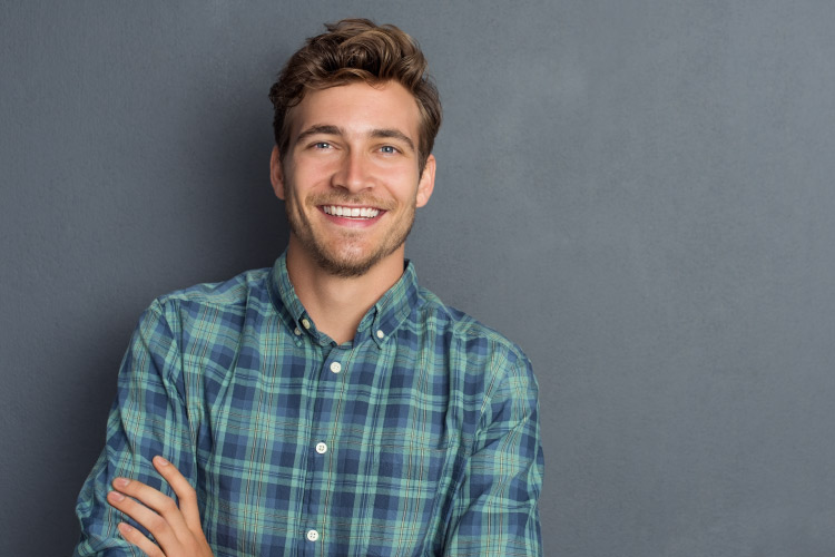 Brunette young man against a gray wall wears a plaid shirt and smiles after receiving professional teeth whitening