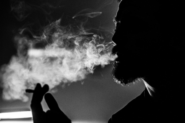 Black and white photo of a bearded man smoking a cigarette with tobacco, which stains teeth