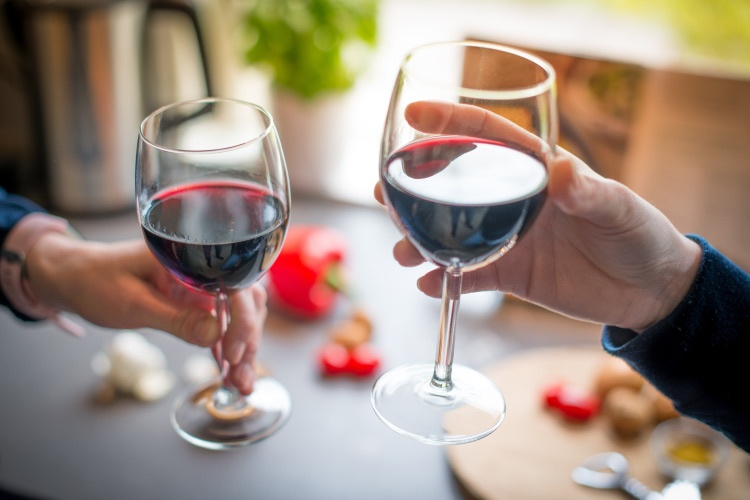 Two hands holding goblets with red wine that can stain teeth