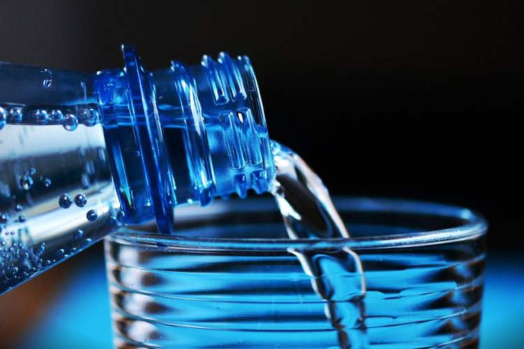 blue background with bottle of water being poured into a glass