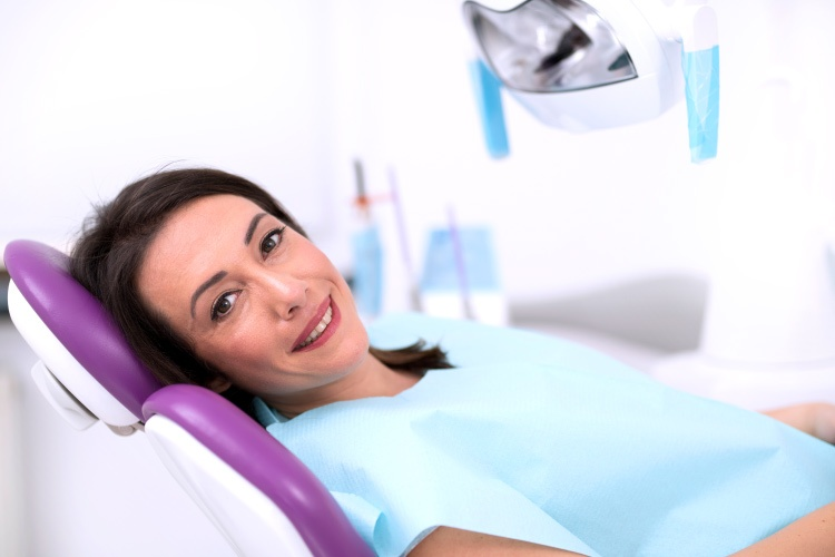 Smiling brunette woman in dental chair awaiting treatment