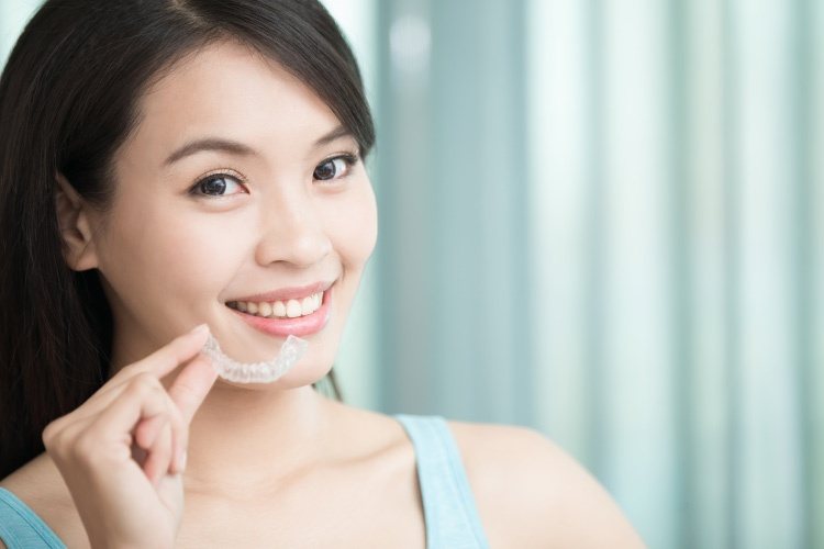 Dark haired girl smiling and holding a clear aligner like Invisalign or ClearCorrect