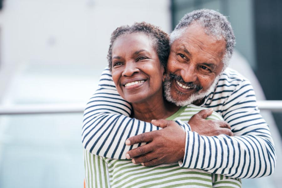 Smiling older black man with his arms around a smiling woman.