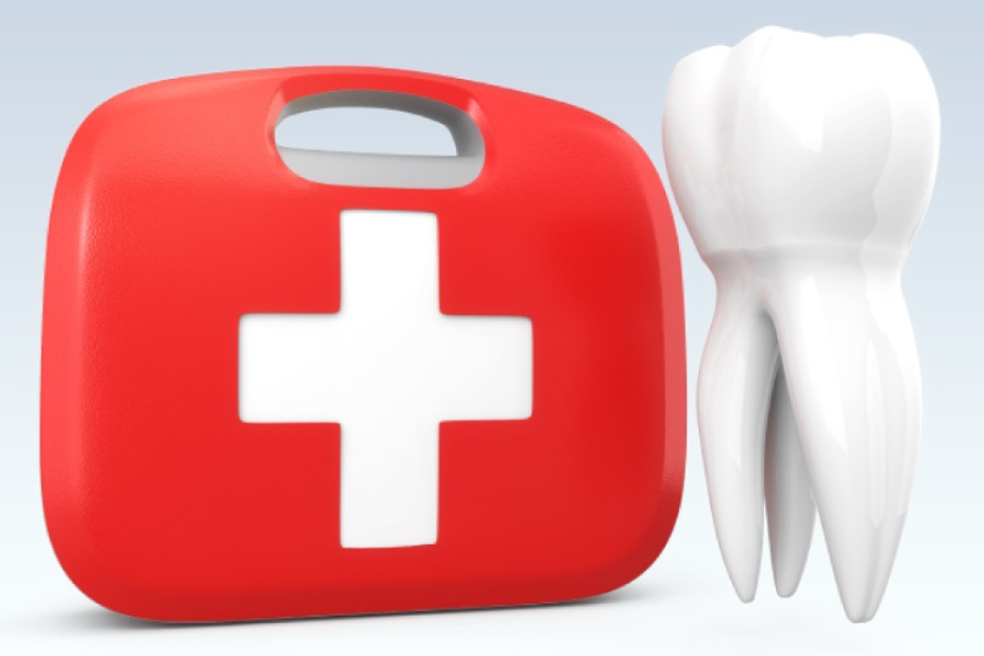 A red emergency kit with a white cross sitting next to a model of a tooth.